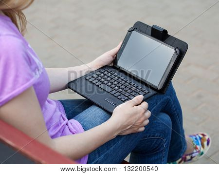 Woman is sitting on the bench outdoors holding a tablet and a keyboard on the knees gray background