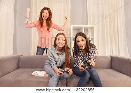 Excited Happy Girls Sitting On Sofa And Playing Video Games