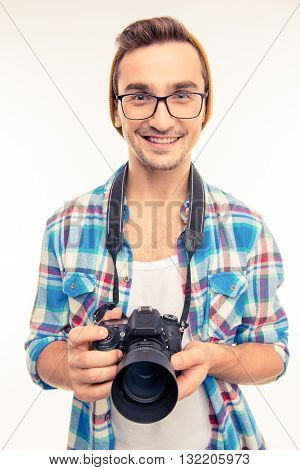 Young handsome photographer taking a photo  on a white background