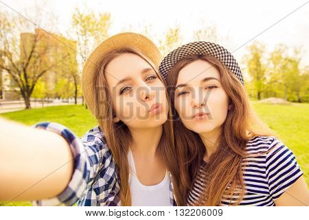 Two Beautiful Girls In Caps Making Selfie And Pouting