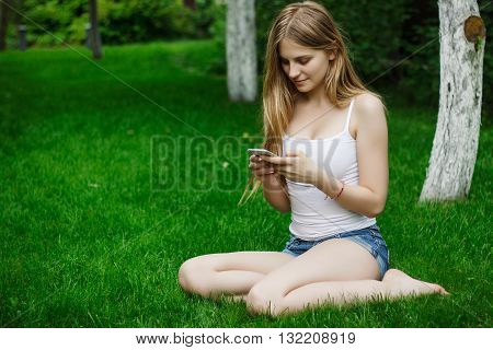 beautiful girl talking on the phone and sitting on the green gra