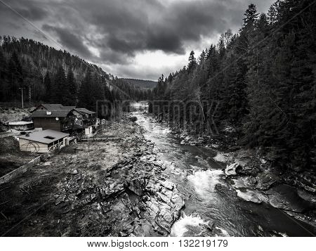 landscape with mountain river and buildings on bank, aerial black and white photo