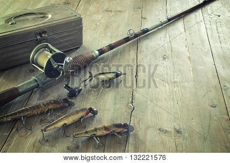 Antique tackle box bait-casting fishing rod and lures on a grunge wood surface