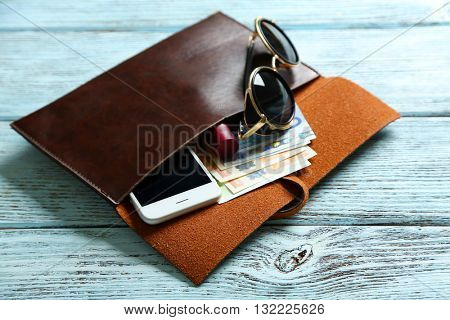Leather purse with glasses, mobile phone and euro banknotes on wooden background