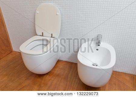 image of white toilet and bidet closeup