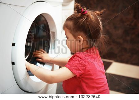 Little girl playing with washing machine