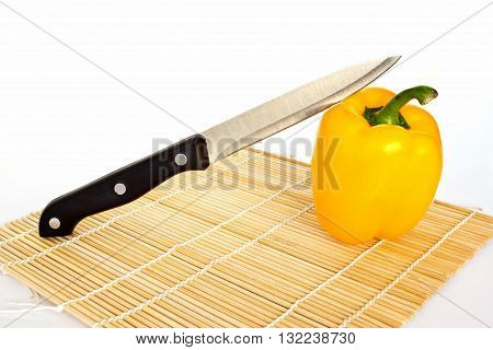 A knife on yellow sweet peppers isolated on a white background