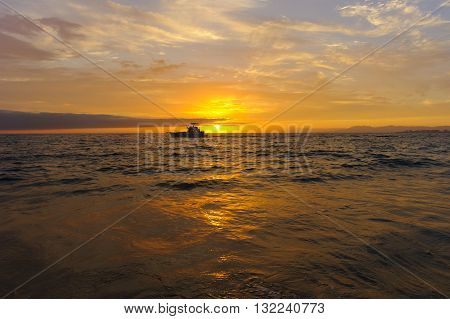 Boat sunset is a sport fishing boat at sunset trolling with fishing poles waiting for a strike.