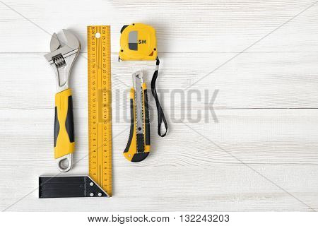 Building tools including centimeter ruler, wrench and cutter placed in the right side on wooden surface with open space. Top view composition. Measurement. Fixing and cropping. Hand tool. Tools for carpentry work. Type of fastener. Mend and repair. Parts