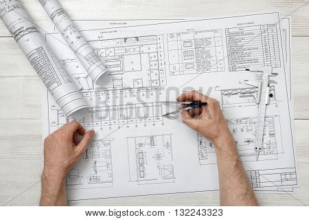 Close-up hands of man holding an engineering divider over drawing plan in top view.  Workplace of architect or constructor. Engineering work. Construction and architecture. Architect drawing. Measurement. Draftsmanship.