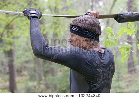 STOCKHOLM SWEDEN - MAY 14 2016: Rear view of man with mud in his face trying to maintain his balance on a slack rope in the obstacle race Tough Viking Event in Sweden April 14 2016