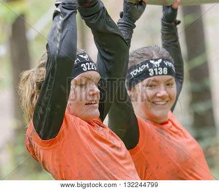 STOCKHOLM SWEDEN - MAY 14 2016: Two smiling woman with mud in her face trying to maintain her balance on a slack rope in the obstacle race Tough Viking Event in Sweden April 14 2016