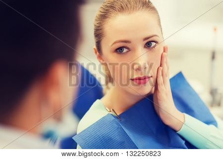 people, medicine, stomatology and health care concept - woman patient talking to male dentist and complain of toothache at dental clinic office