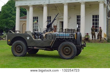Silsoe, Bedfordshire, England - May 30, 2016: World War 2 Jeep mounted Machine gun men in ww2 military uniforms with red berets in front of old building.