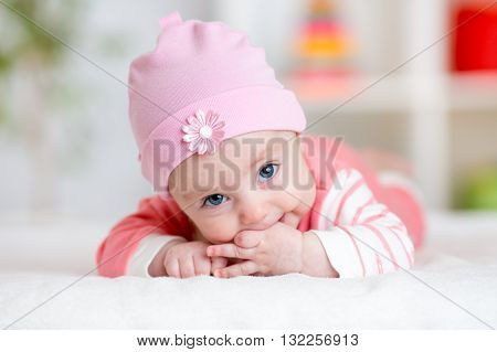 Baby teething sucks fingers. Infant kid lying in nursery room poster