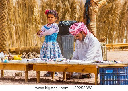 Sharm El Sheikh Egypt - May 07 2014: Bedouin and his daughter keep souvenir shop in desert.
