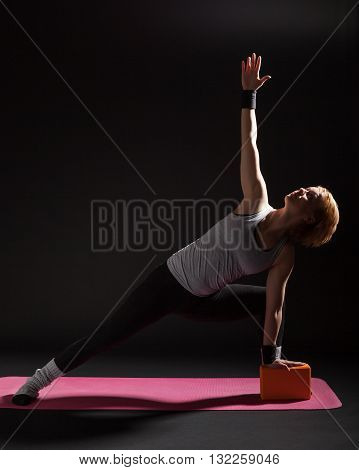 Young woman practicing yoga, Trikonasana / Bikram triangle left
