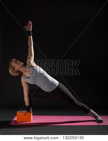 Young woman practicing yoga, Trikonasana / Bikram triangle right