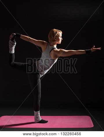 Young woman practicing yoga, Natarajasana / Shiva posture pose