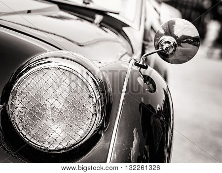 Shiny vintage car. Detail view of the headlight. Retro car. Black and white photo. Front light. Retro automobile scene. Circle headlamp.