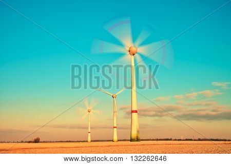 Modern Wind Turbines Producing Energy In Sunny Spring Morning. Vintage Style Toned Effect