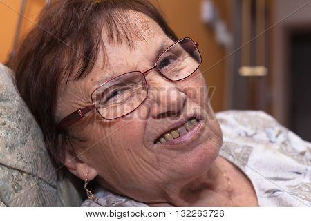 Closeup of a senior woman grimacing and frowning.