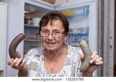 Happy senior woman holding pork liver sausages while standing in front of the open fridge in the kitchen.