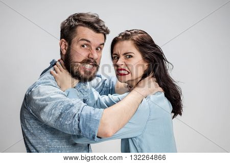 The quarrel and strangling men and women on gray background
