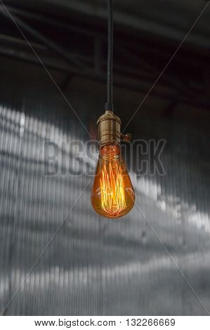 Vintage hanging light bulb over gray room stock photo