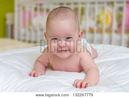 Cute And Smiling Crawling Baby Girl Lying On Belly.