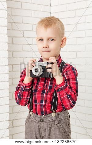 Little boy with retro camera in hand. Closeup