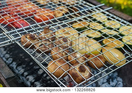 Fresh mushrooms and vegetables grilling in gridiron picnic in summer outdoors