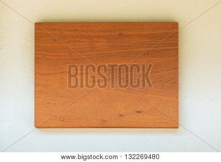 Blank wooden signboard on cement wall with shiny under roof.