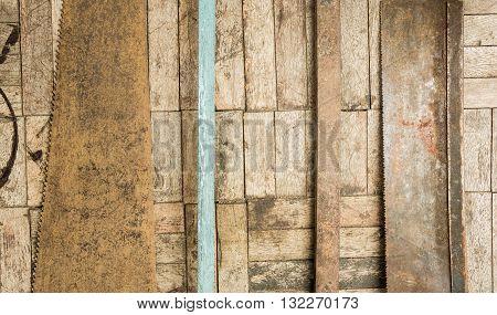 set of hand saw blade teeth on wooden parquet background