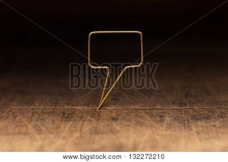 Golden tweet or remark. Blank speech bubble made of gold wire on rustic or grunge wood ready for inserting text. Dark background. Shallow depth of field.