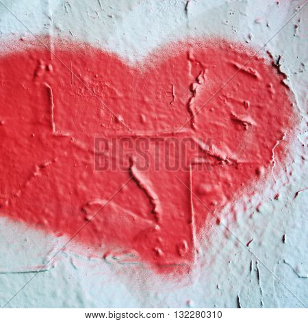 Pink heart shaped symbol on the concrete wall. Urban wall close-up. Bright paint on concreat surface. Can be frame for text. Aged photo. Street graffiti close up. Color wall macro background.
