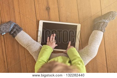 top view of a toddler in green shirt playing with a tablet device on a wooden floor