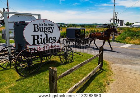 Strasburg PA- May 29 2016: Buggy Rides sign includes an actual Amish buggy near Strasburg in Lancaster County PA.