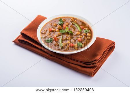 spicy chick peas also known as Chola Masala or Chana Masala or Chole served with fried puri, pickle and green salad