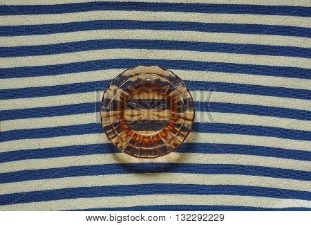 Brown glass saucer on blue white textile