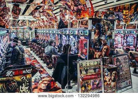 Tokyo Japan - February 26 2015: People play on arcade machines in Pachinko Arcade Games Hall