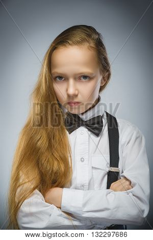 Portrait of calm and mistrust girl isolated on gray background. Normal human emotion, facial expression. Closeup.