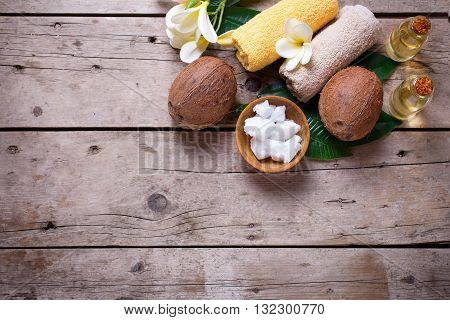 Coconuts coconut oil and towels on vintage wooden background. Spa setting. Selective focus. Natural organic spa products. Place for text. Flat lay.