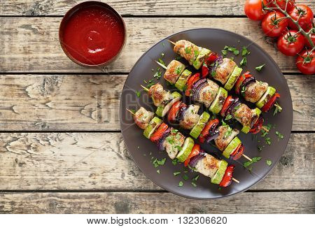 Homemade turkey or chicken meat shish kebab skewers with ketchup sauce, and tomatoes on rustic wooden table background. Traditional barbecue grill shish food