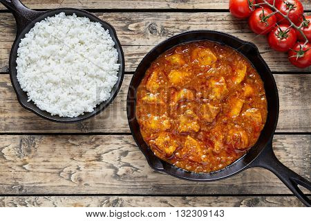 Traditional chicken tikka masala Indian spicy meat food with rice in cast iron skillet on vintage wooden background