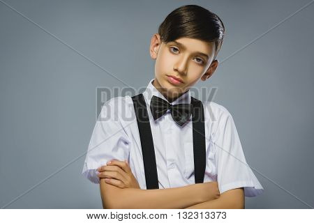 Portrait of calm and mistrust boy isolated on gray background. Normal human emotion, facial expression. Closeup.