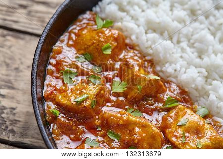 Chicken tikka masala traditional Indian spicy curry national meat food with rice and parsley in cast iron skillet on vintage wooden background. Karahi chicken or korma vindaloo recipe.