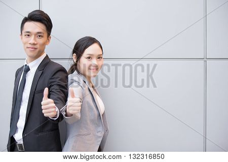 Business people team smile show thumb up in the office shot in Hong Kong asian woman and man