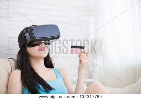 Smile happy woman shopping online by VR headset glasses of virtual reality at home asian beauty