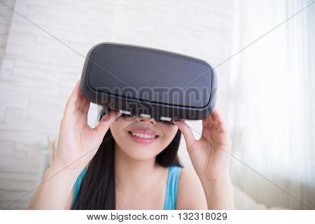 Smile happy woman getting experience using VR-headset glasses of virtual reality at home asian beauty
